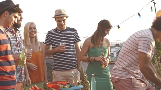 vidéos et rushes de servant des boissons à des amis au cours de la partie sur le toit - man drinking terrace