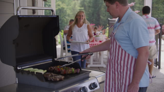 serving food from grill at backyard barbeque - alla griglia video stock e b–roll