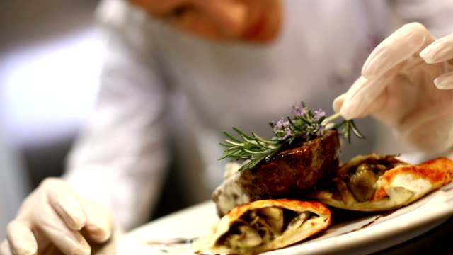 Serving food. Professional female chef placing finishing touches by putting rosemary on steak just before serving. She's wearing protective gloves when touching ready to eat food.HD 1080 commercial kitchen stock videos & royalty-free footage