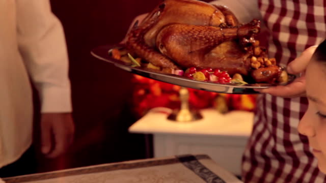 Serving Thanksgiving Turkey Young mother serving thanksgiving turkey for her family turkey stock videos & royalty-free footage