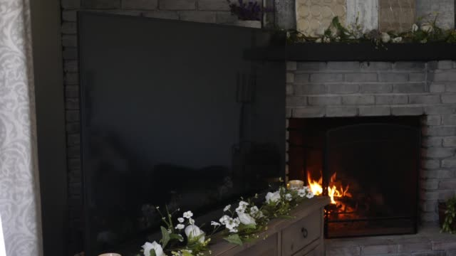 A 4K TV set in modern living room with warm fire burning in background