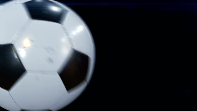vídeos de stock e filmes b-roll de set of 4 videos. beautiful soccer ball hits the camera in slow motion on black with flares. football 3d animations of flying ball. - chutar