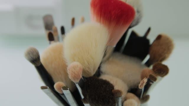 vidéos et rushes de ensemble de brosses pour le maquillage sur la table dans le vestiaire. industrie de la mode. défilé de mode backstage - fard à paupières
