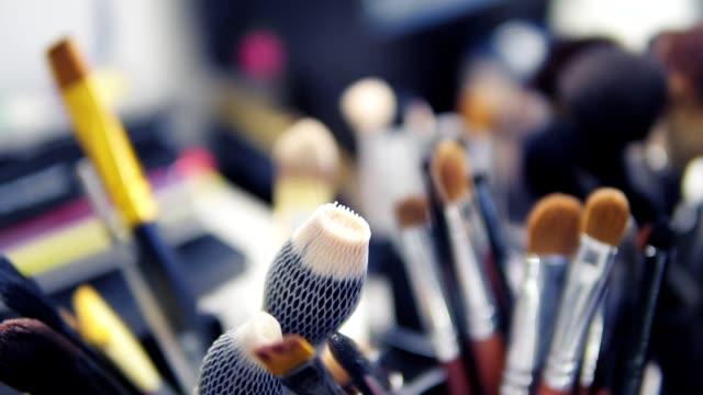 Set of brushes for make-up on table in dressing room. Fashion industry. Fashion show backstage. Slowmotion shot video