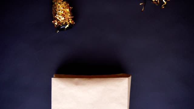 A set of items for the New Year party are moving on a black table. Top view, Removed in stop motion