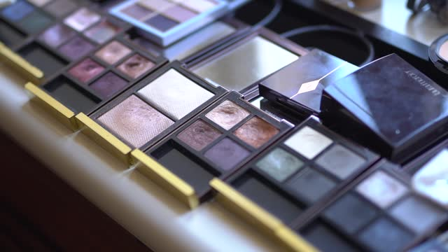 A set of professional decorative cosmetics laid out on the table, eye shadow palettes