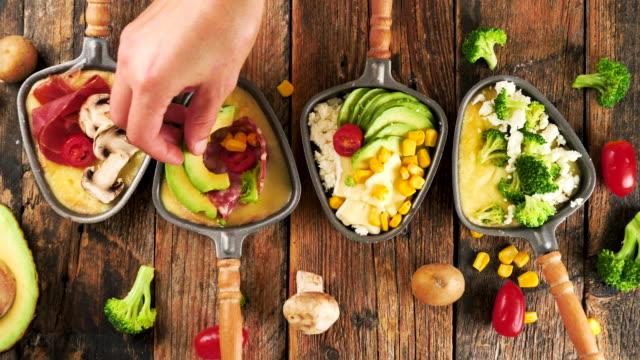 vidéos et rushes de ensemble de fromage raclette avec légumes et salami - raclette