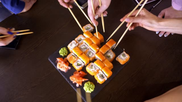 A set of sushi rolls on a table in a restaurant. A party of friends eating sushi rolls using bamboo sticks. video