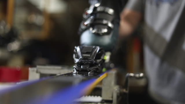 setting bindings in ski rental and repair shop in various stages of production series - negozio sci video stock e b–roll