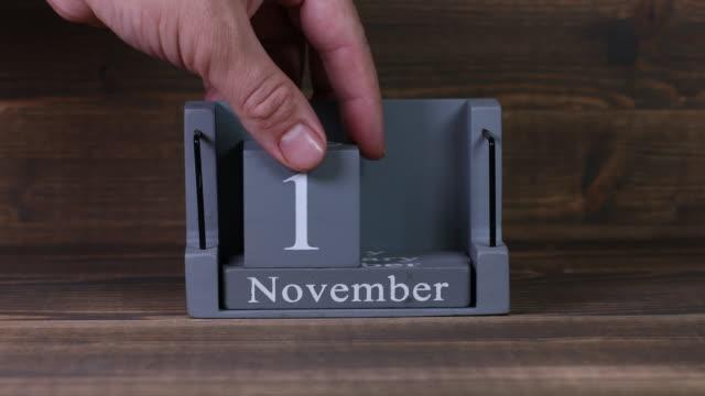 10 setting date on wooden cube calendar for november months - ноябрь стоковые видео и кадры b-roll