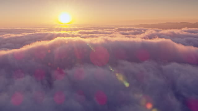 AERIAL Setting sun coloring the fluffy clouds in pink Aerial shot above the fluffy clouds being colored in pink by the setting sun. Shot in USA. perfection stock videos & royalty-free footage