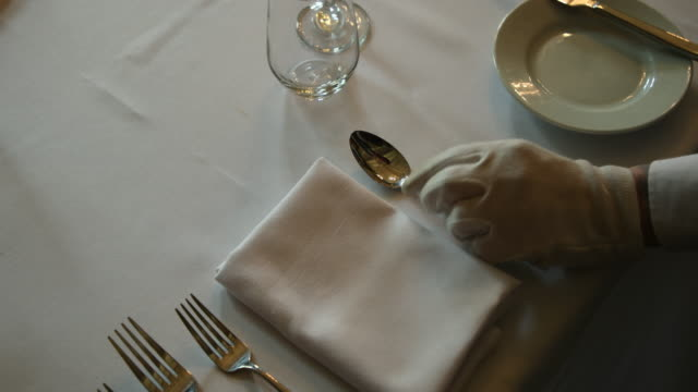 Setting the Table A waiter is carefully placing crockery on a tablecloth in a luxury hotel. wait staff stock videos & royalty-free footage