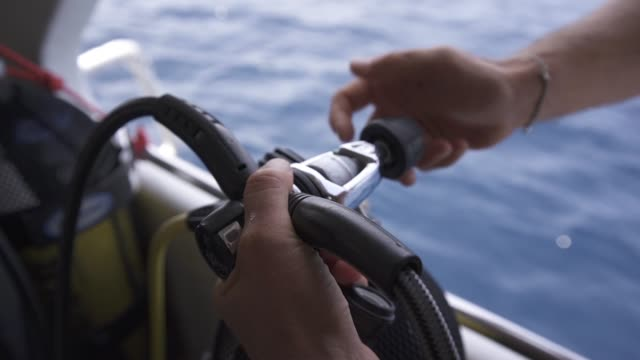 Setting up Setting up the scuba gear, placing the regulator on the valve of the tank aqualung diving equipment stock videos & royalty-free footage