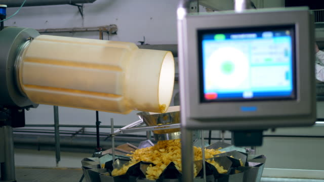 settings of chips-producing mechanism are being regulated by a lady - приготовленный картофель стоковые видео и кадры b-roll