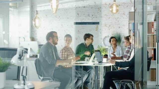 stockvideo's en b-roll-footage met zeven stijlvolle mensen die planning sessie zittend aan grote tafel in hun creatieve kantoor. - marketing