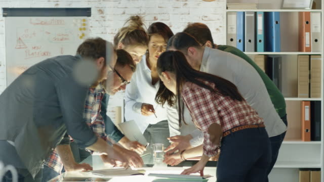 Seven Stylish Standing Diverse People Lean on a Conference Table While Energeticaly Discussing Daily Business Plans. – Video