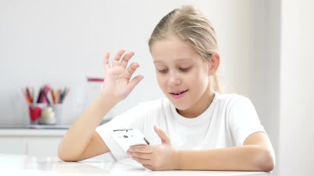 sju år gammal tjej med smartphone. - endast flickor bildbanksvideor och videomaterial från bakom kulisserna