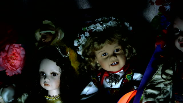 Several dolls on a shelf of an old house in dramatic lighting,