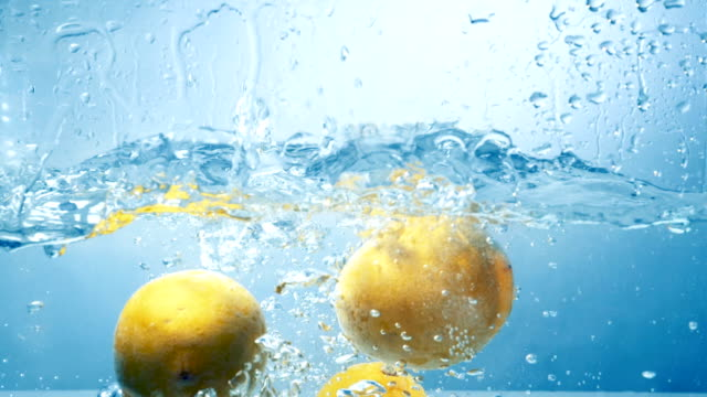 Several lemon fruits fall inside a water tank and disturb water. video