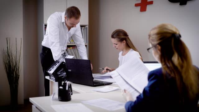 vidéos et rushes de plusieurs personnes regardent les documents dans le bureau, l'homme et la femme travaillent dans un cabinet d'avocats, ils compilent des rapports sur l'ordinateur - notaire
