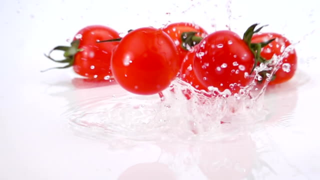 A Several Ripe Tomatoes are Falling on the Table video