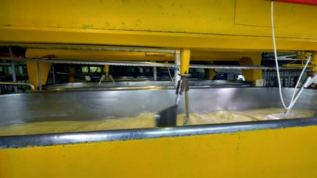 mehrere reihen von gelbe milch bottiche mit metall rührwerken. - milchkrug stock-videos und b-roll-filmmaterial