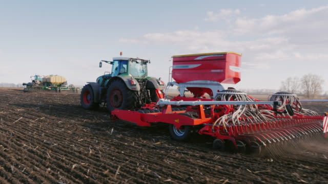 Several seeders in the field are sowing wheat. Field work in the spring, agribusiness video