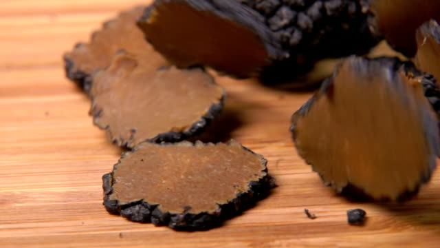 Several slices of a black truffle mushroom are falling on the board - video
