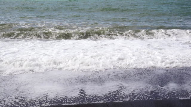 Several small waves roll on a sandy beach video