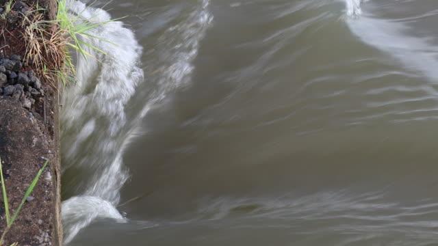 Severe flooding streams flowing underneath a concrete bridge. video