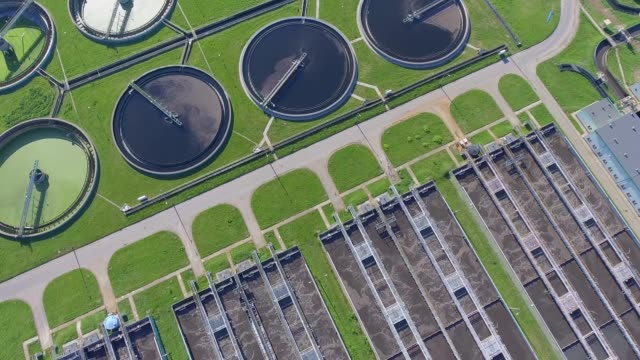 sewage farm. static aerial photo looking down onto the clarifying tanks and green grass. - acquedotto video stock e b–roll