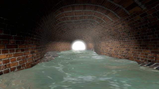 vídeos de stock e filmes b-roll de sewer tunnel with light at the end - material de construção