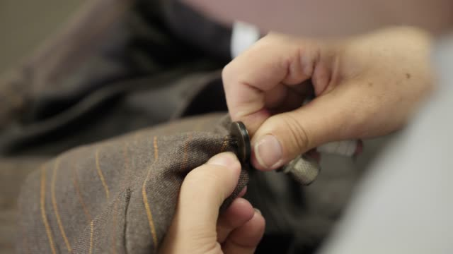Sewing a button onto a brown jacket tailored suit Sewing a button onto a brown jacket tailored suit in the atelier room. Close-up shot art and craft product stock videos & royalty-free footage
