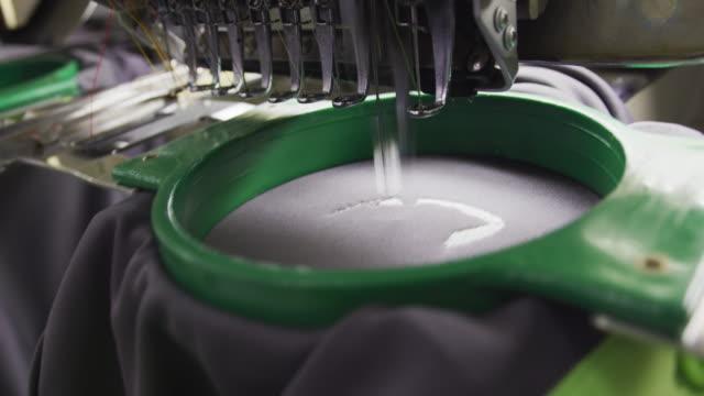 sewing machine manufacturing clothes in factory - sprzęt sportowy filmów i materiałów b-roll