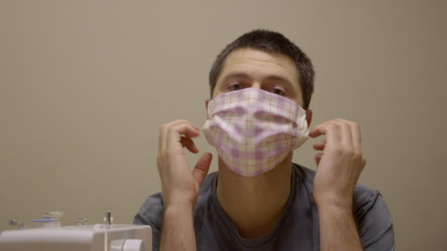 sewing medical masks for hospitals at coronavirus pandemic time. - face mask stock videos & royalty-free footage