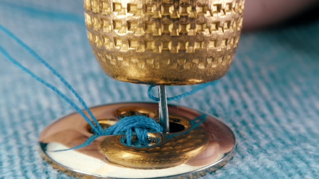 sewing needle with a blue thread sews a button of gold color - tailor working video stock e b–roll