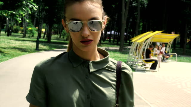 sexual woman with red lips in mirror sunglasses walks at the park video