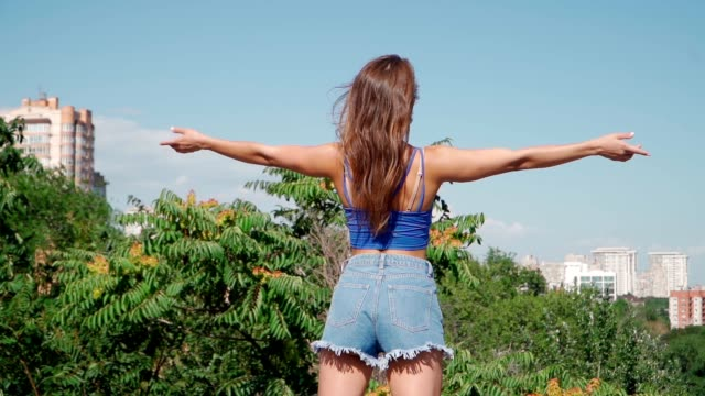 Sexy and Slim young woman in short denim shorts hands up on the background city on a summer sunny day. Athletic Girl with a Perfect figure. Diet and nutrition. Beautiful booty, close up.