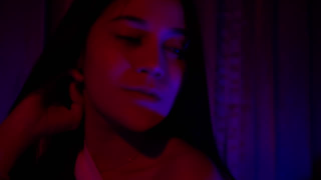sexy asian looking at the camera in red and blue light at night video