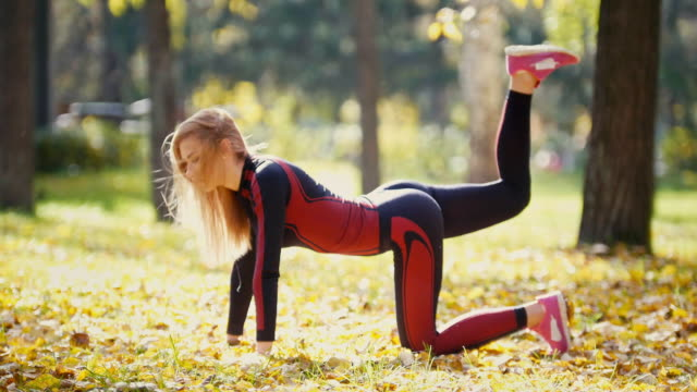 Sexy Attractive female blonde bikini-fitness model stretching in the autumn park on ground covered yellow leaves - leg lifts Sexy Attractive female blonde bikini-fitness model stretching in the autumn park on ground covered yellow leaves - leg lifts, telephoto bodyweight training stock videos & royalty-free footage