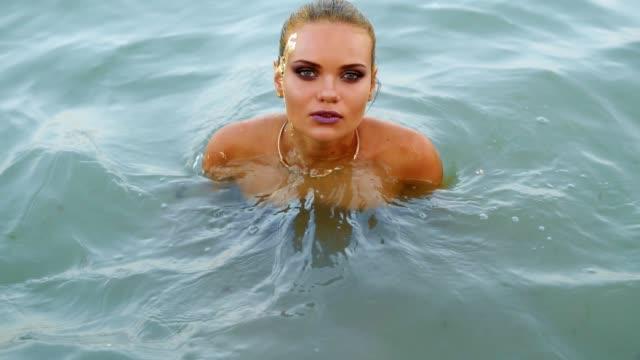 sexy attraktive frau im wasser am strand den kopf aus dem wasser zu heben und in die kamera schauen und flirten mit dem betrachter. verführerische junge frau mit goldenen make-up und pferdeschwanz - strandmode stock-videos und b-roll-filmmaterial