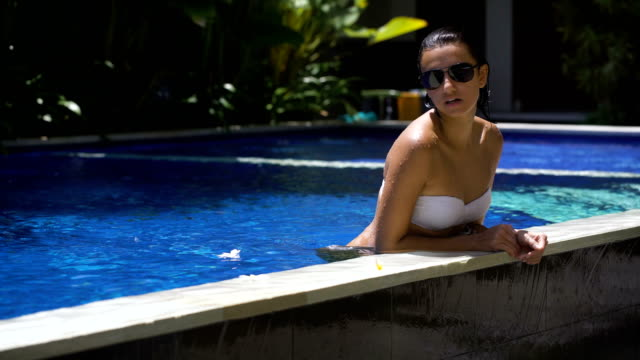Sexy beautiful girl in white bikini and black sunglasses is enjoying her time in the swimming pool. Young woman is lying up to the waist and then dipping into the water video
