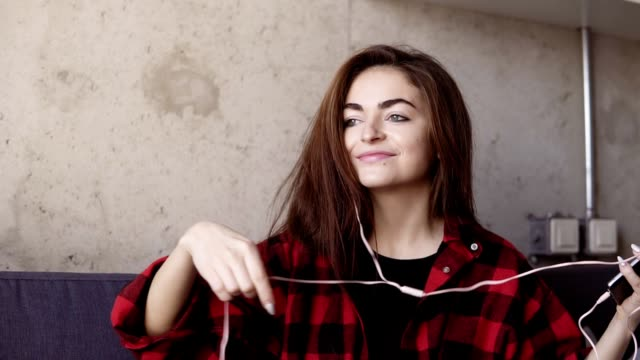 Sexy beautiful young girl puts headphones in her ears and starts dancing to some music. Slow motion footage. video