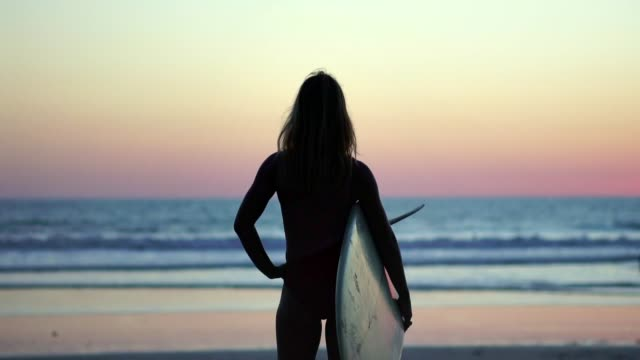 Video Sexy blonde surfer girl on a beach holding her surfboard, looking for waves to surf