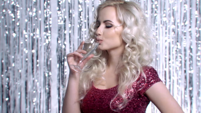 Sexy blonde woman toasting champagne over glittering background. Cute young woman in pink shiny dress during new years party drinking champagne. vanity stock videos & royalty-free footage