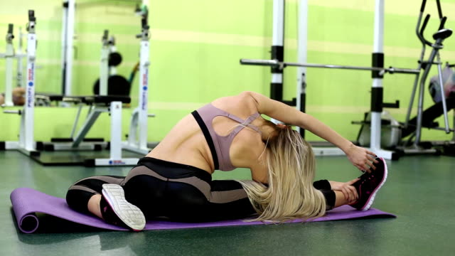sexy blonde young woman warming up before training in a  gym. - donna forzuta video stock e b–roll