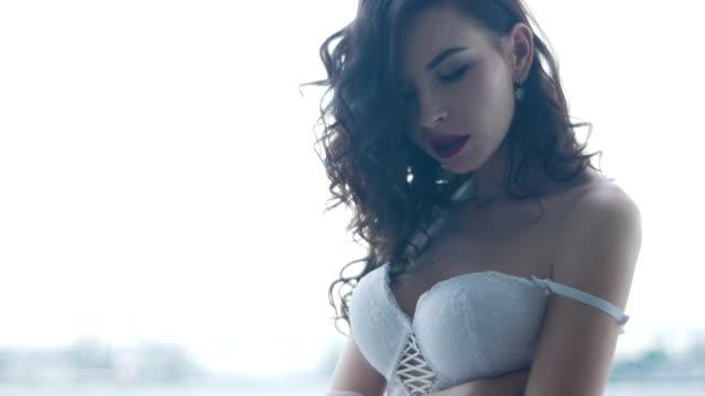 fille brune sexy se dresse en soutien-gorge corset blanc - Vidéo