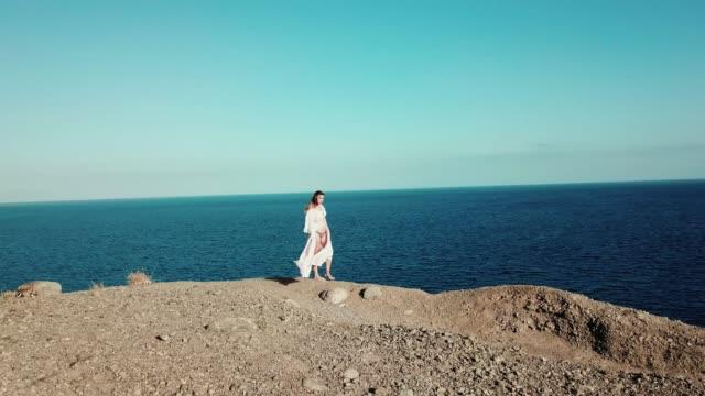 sexy brünette in bikini ist fuß entlang dem rand der klippe mit wind spielt mit ihrem haar und schöne landschaft auf blauen himmel und das meer genießen. - horizont über wasser stock-videos und b-roll-filmmaterial