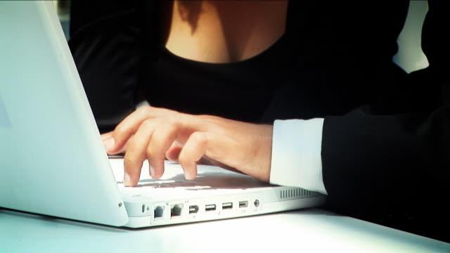 vidéos et rushes de sexy femme d'affaires avec un homme à l'aide d'un ordinateur portable - décolleté