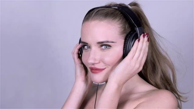 sexy caucasian woman with headphones listening music, slow motion. - djurarm bildbanksvideor och videomaterial från bakom kulisserna